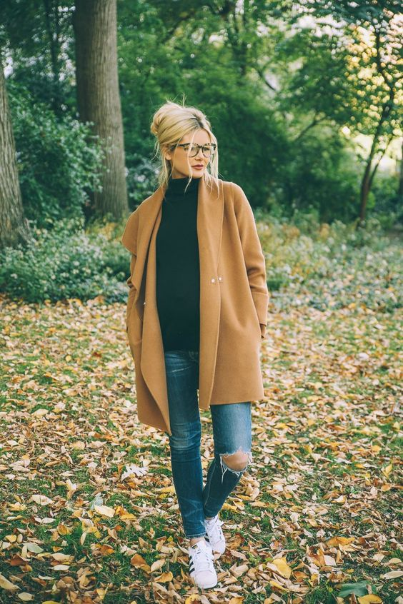 Camel coat, distressed jeans, black sweater, white sneakers. Simple and comfortable but still stylish, especially with the updo and red lipstick.: