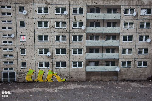 The artist has transformed a dozen or so concrete barricades into a tower block city complete with satellite dishes, tagged up walls and graffiti.