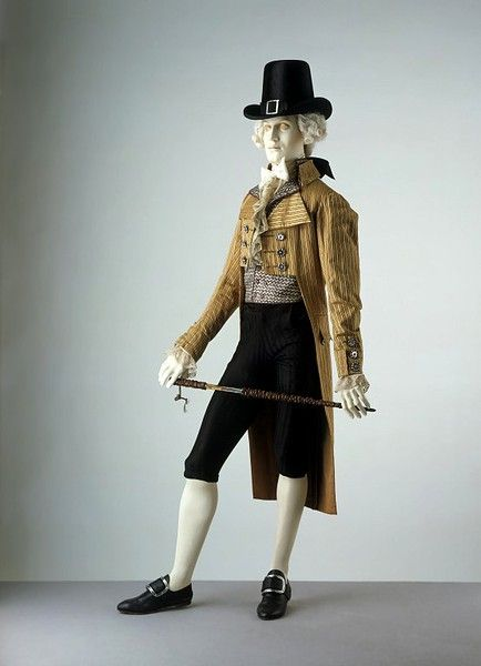 This double-breasted coat demonstrates the exaggerated style of the late 1790s. It has a very high turned-down collar and large revers (lapels). The coat is now cut straight across in front and, following the example of women's dress, the waistline is several inches above the natural level. The double-breasted style in both coats and waistcoats was a fashion that began in the 1780s. The fabric of this coat is poplin, a blend of silk and worsted (wool), popular for summer wear. The coat is…