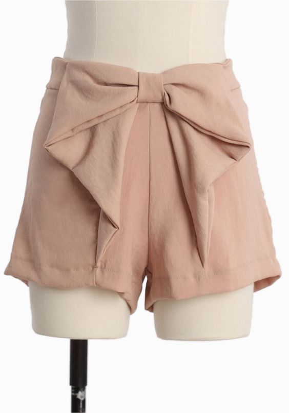 "Romana Dream Bow Shorts In Peach 34.99 at shopruche.com. The feminine bow detail imparts romance to these lightweight peachy-beige shorts. Finished with an elasticized waist for a flattering and comfortable fit.  100% Polyester, 12"" length from top of waist, Made in USA"