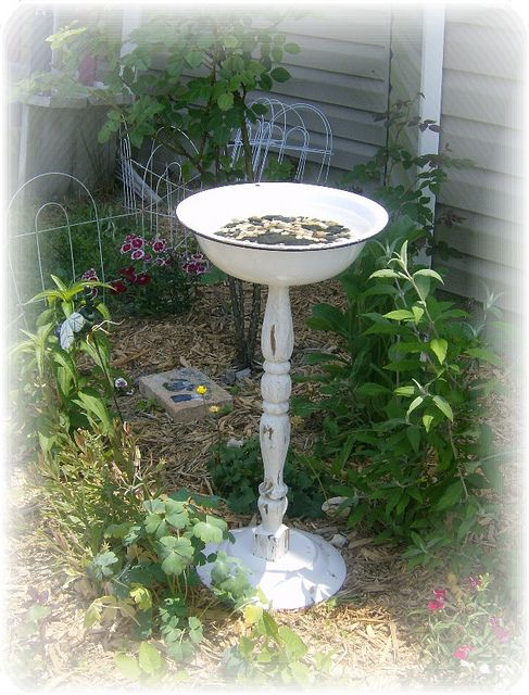 Birdbath made from old table leg attached to upside down plate as base and enamel basin on top: