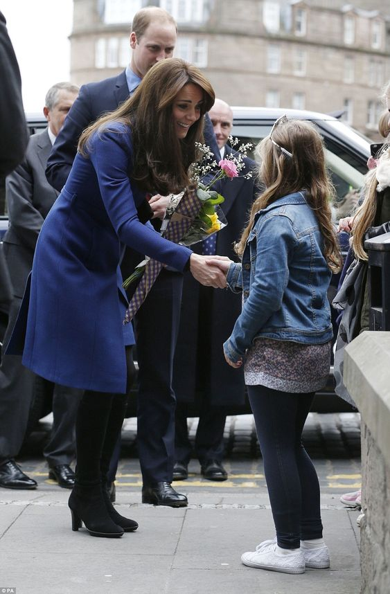 The Duke and Duchess of Cambridge arrive for the visit to The Corner and meet young wellwishers, who presented the Duchess with a colourful bouquet of flowers: