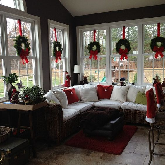 Love the wreaths suspended with red ribbon in the windows of this sunroom decorated for Christmas. Do this in my front windows. Read More at: drix34.blogspot.com