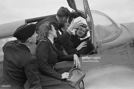 Pilots and engineering officers of the ATA (Air Transport Auxiliary) hold a discussion in the cockpit of a Percival Proctor training aircraft at the Elementary Flying Training School at Thame, Oxfordshire, September 1944. ATA pilots are trained to deliver newly manufactured aircraft from the factory to military airfields. Original publication: Picture Post - 1805 - The Work Of The Ferry Pilots - pub. 16th September 1944.