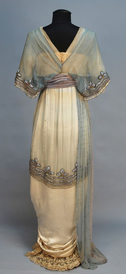 LUCILE, LADY DUFF GORDON BEADED and APPLIQUED SILK GOWN, c. 1914. Cream satin having cream and blue chiffon short sleeve bodice with V-neck and back, trimmed in bands of blue satin, silver metallic cord and crystal beaded fringe and colorful silk flowers, blue satin cummerbund, hobble skirt beneath short beaded chiffon overskirt ruched in front to reveal beaded lace and chiffon underskirt and having silk flower swag, chiffon side drape studded with rhinestones.