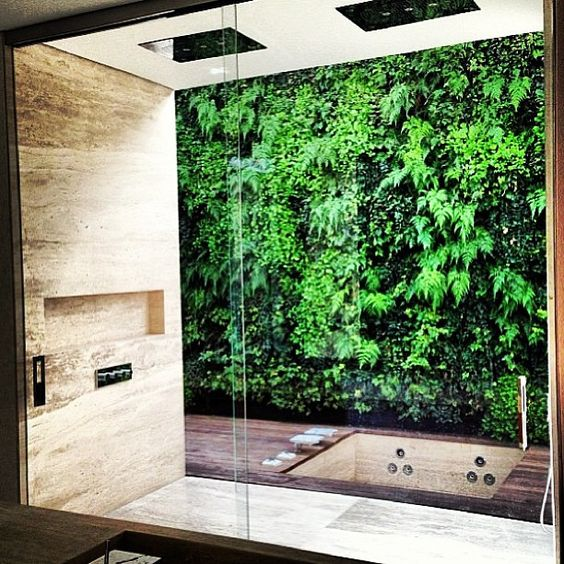 Private indoor shower with vertical garden view for Garden bathroom ideas