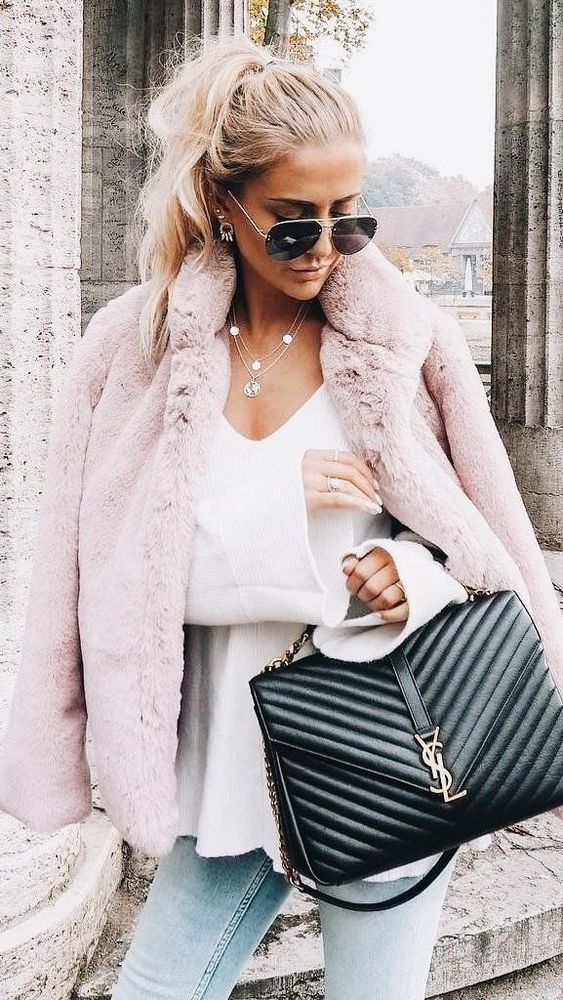 Cozy pink jacket over cute white top with blue jeans and chic black handbag.