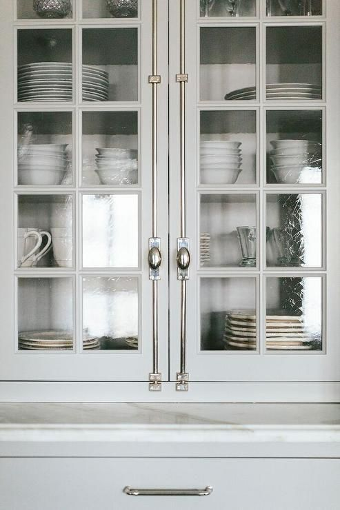 White and gray kitchen features floor to ceiling glass seeded china cabinets fitted with glass cremone bolt doors.