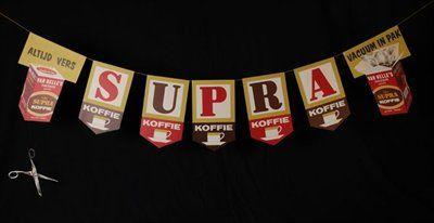 """Slinger met vlaggen """"Supra"""" koffie van Van Nelle, onderaan een schaar"""