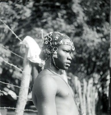 Africa | An upper body profile portrait of a Mandari youth with elaborate beaded hair ornaments tied into the hair, as well as a band of beads across the forehead and under the chin. Bahr el Jebel Tali, Southern Sudan | Photo taken by Jean Carlie Buxton, 1950 - 1952