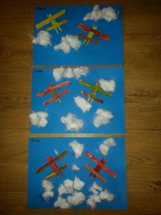 Thema vervoer; vliegtuigjes van wasknijpers en ijsstokjes. Dit keer op blauw papier geplakt en wolken erbij gemaakt.