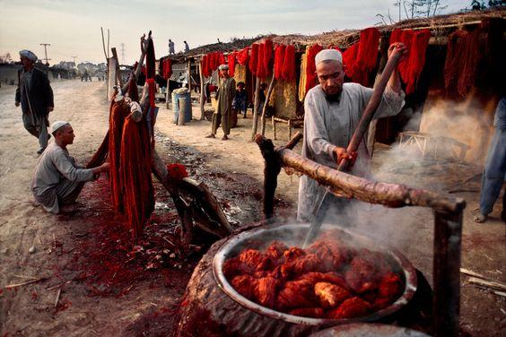 Afegãos a tintar lâ para os tapetes na fronteira entre o Paquistão e o Afeganistão