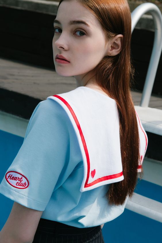Look amazing and youthful with this classic sailor collar top! The shirt's collar is in contrast color for noticeable style with a border and heart embroideries as accents. It also comes with short sleeves, a logo detail, and a comfortable fit. Wear it wi