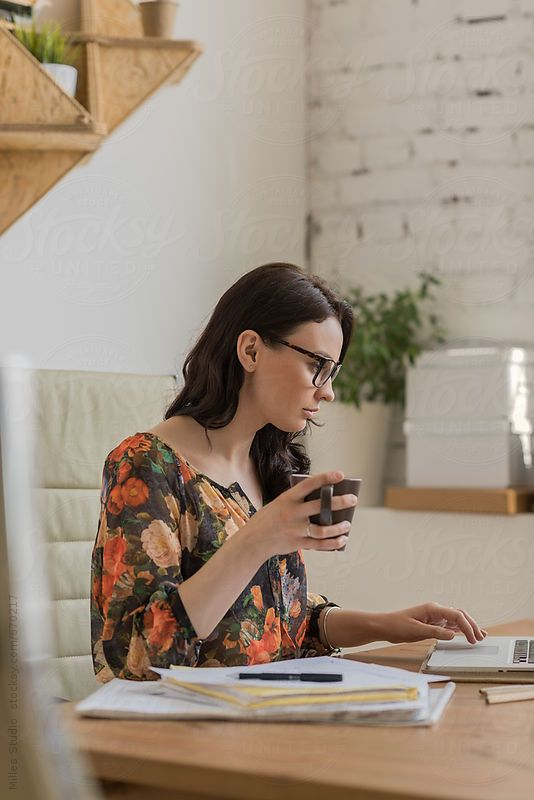 Business woman at office drinking coffee while working with papers and laptop: