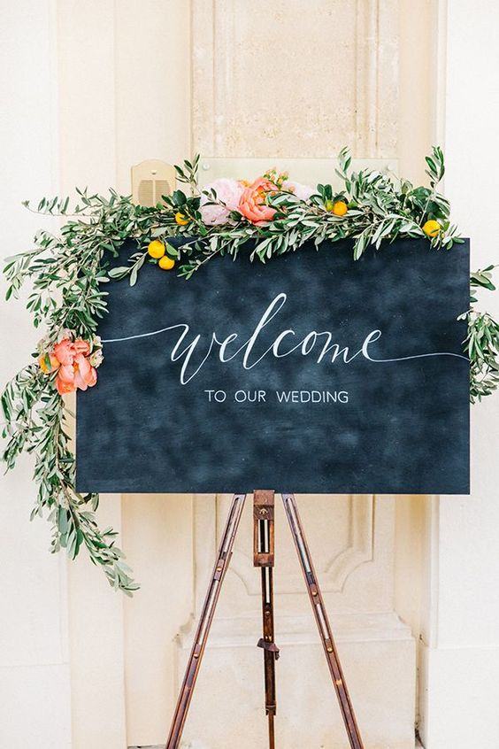 Festively framed by lemon and olive branches studded with giant pink peonies, a calligraphed chalkboard sign welcomed guests, who had come from Sweden, Poland, and different parts of Austria. They were also greeted with glasses of Uhudler sparkling wine, an Austrian speciality, which the couple had enjoyed on their first date. | Photo by Tony Gigov