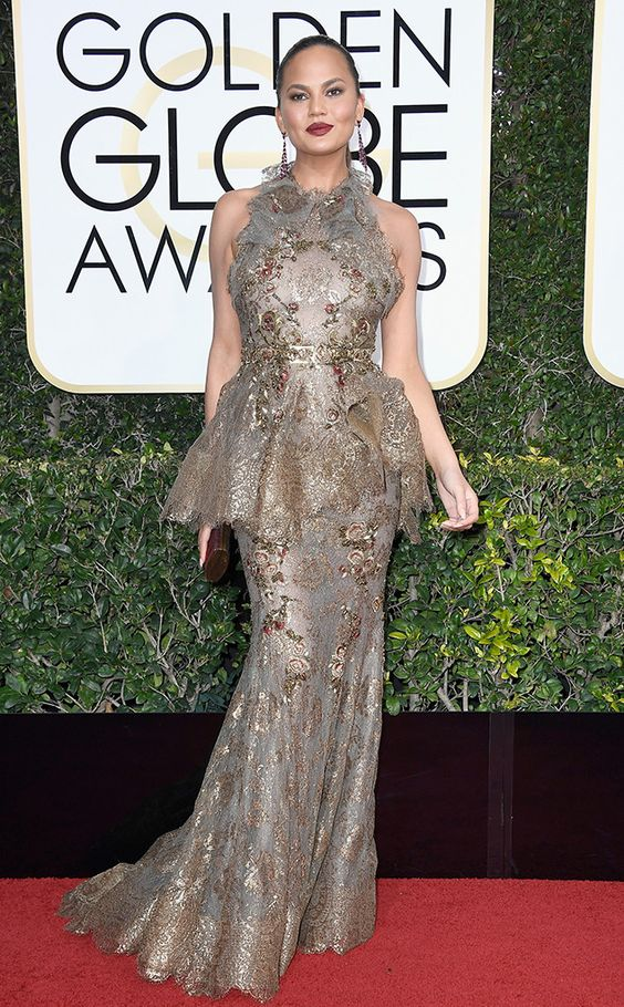 Chrissy Teigen in a silvery gold, sheer, floor length dress, halter neckline, gold embroidery with green and red rose patterns, so lovely! :D and hair sleeked back to show long dangly earrings. Beautiful makeup with a dark velvety red lipstick.