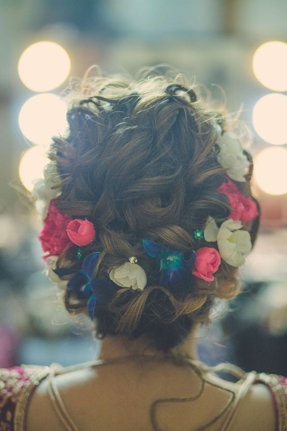 Wedding Hairstyle With A Curly Bun And Multicolour Flowers Indian Bridal Hairstyles Curly Hair Styles Hair Styles