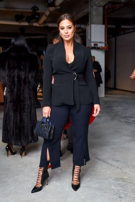 O estilo de: Ashley Graham. Blazer preto, regata preta, calça de alfaiataria com fenda, ankle boot lace up