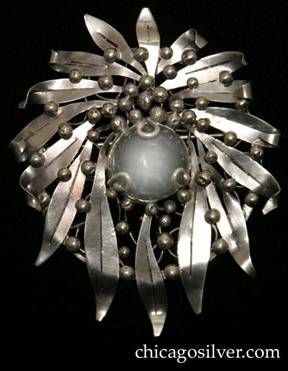 Mary Gage pin, round, composed of a wreath of long, thin outward-pointing chased leaves on a circular frame strengthened with irregular wire...