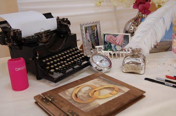 Gästebuch. Die Dekoration mit einer alten Schreibmaschiene, Kompass und das Bild des Brautpaares.