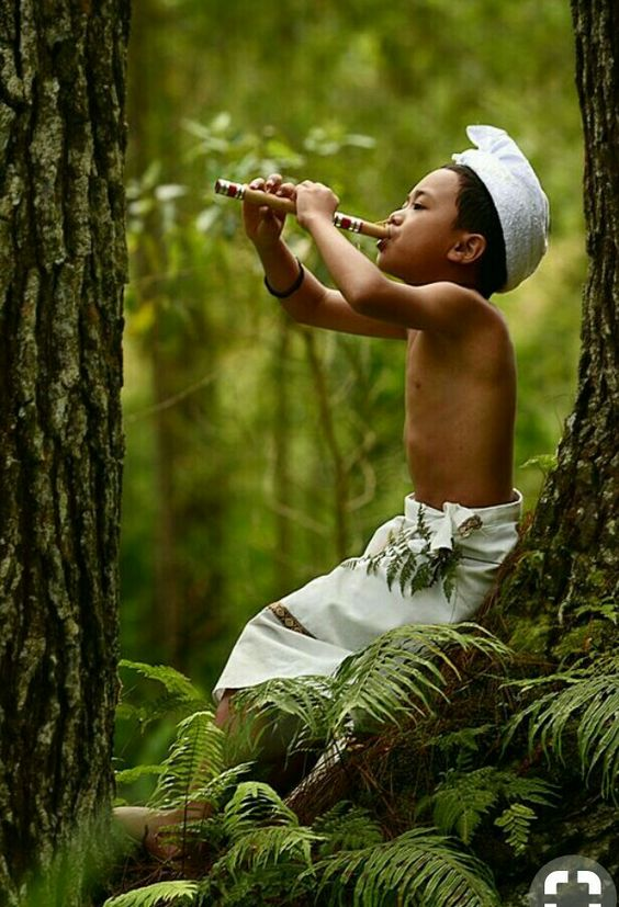 Young south Asian boy playing the flute in the forest.