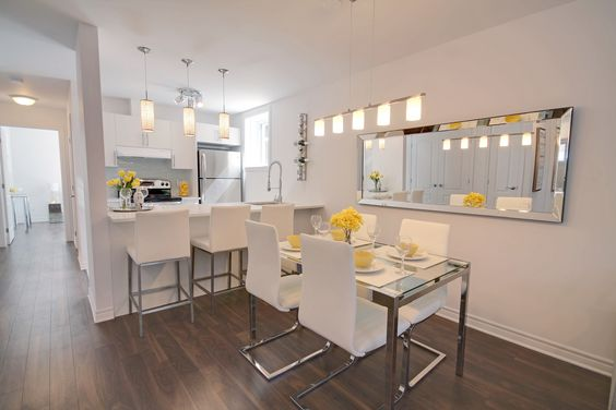 Living room and kitchen staged - model condo - basement unit with alot of natural light - colours are yellows and white and gray.  Le Desaulniers condos in Montreal