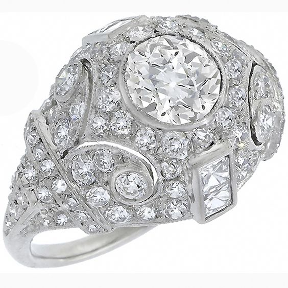 This is a gorgeous platinum diamond ring from the Edwardian era. The ring is centered with a sparkling GIA certified round old European cut diamond that weighs 0.93ct. The color of the diamond is J with SI1 clarity. The center diamond is accentuated by smaller old mine cut and French cut diamonds that weigh approximately 2.00ct and 0.50ct respectively