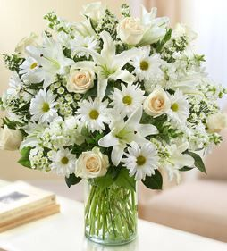 Sincerest Wishes White Arrangement Express your heartfelt wishes with our elegant all-white arrangement of roses, lilies, stock, daisy poms and monte casino. •This item is handcrafted especially for y