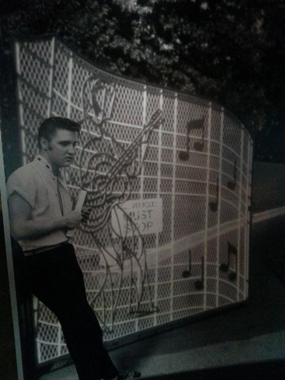 PHOTOSHOP! This image of Elvis that was taken by Lloyd Shearer in Memphis in late July 1956 has been photoshopped into the picture of the open Graceland gates. As we all know, Elvis purchased Graceland in March 1957. ;-)