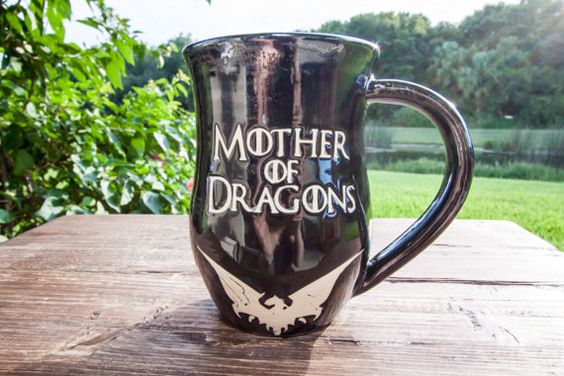 "Handmade Game of Thrones Mug - Mother of Dragons  Season 6 is over, but help keep the spirit alive for Game of Thrones with this Game of Thrones inspired handmade stoneware mug. This mug is perfect for everyday use. It says ""Mother of Dragons"" on the front with a glossy black and silver base glaze. The Mother of Dragons design and text reveals the unglazed beautiful white stoneware.  - Holds approximately 14-16 ounces - White stoneware - Food safe - Microwave safe - Dishwasher safe"