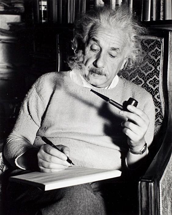 パイプを片手にペンを執っているアルベルト・アインシュタインの壁紙・画像