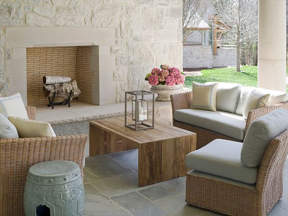 Outdoor living area with limestone fireplace and beautiful patio furniture. Interior design by Phoebe Howard. #patio #loggia #limestone #fireplace #furniture #outdoorliving