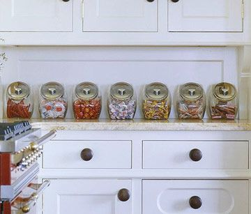 Use Candy Jars for Kitchen Storage             Reminiscent of a candy shop, a row of candy-filled jars lines the countertop in this kitchen. You can find these gallon-size penny candy jars online, or check restaurant supplies shops. They're good for storing dry cereals, pet foods, and salty snacks, too