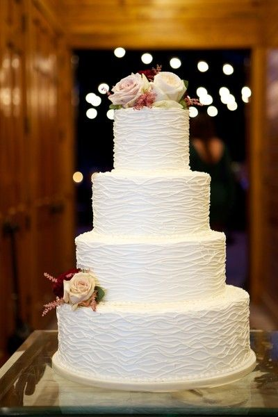 A four-tier, ruffled white fondant-frosted wedding cake decorated with fresh roses - simple yet elegant {Arden Photography}