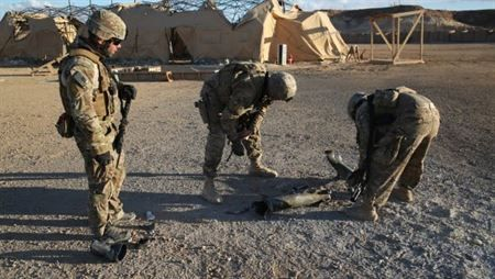 AL ASAD, Iraq - Cpl. Mike Smith (left), Staff Sgt. Steve Fitzpatrick (center), and Spc. Kevin Braun (right), members of a U.S. Army Explosive Ordnance Disposal Company, Task Force Al Asad, examine the point of impact of a 122 mm rocket aboard Al Asad Airbase, Iraq, Jan. 4, 2015. Soldiers and Marines are taking prudent measures to protect the members of Task Force Al Asad from the threat of indirect fire. Photo By: Cpl. Carson Gramley
