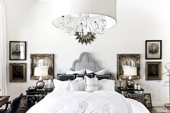 gilded side tables and mirrors for flank a monogrammed bed.