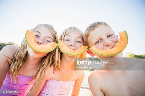 Foto de stock : Caucasian children eating cantaloupe slices