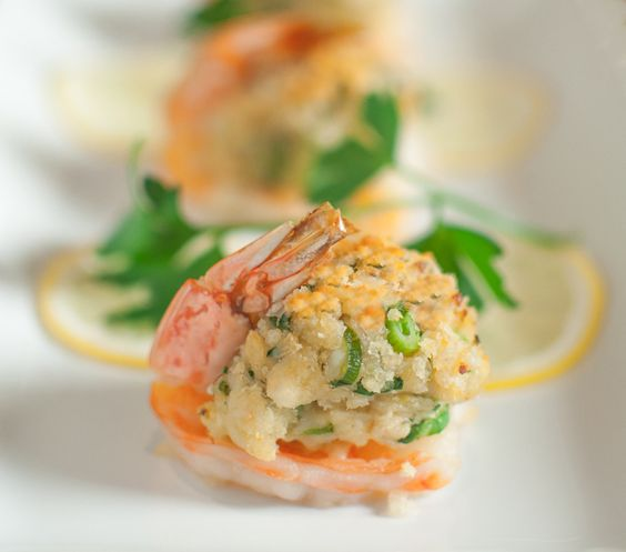 Crab Stuffed Shrimp | Southern Boy Dishes 24 jumbo shrimp 1 lb lump crab meat 1 cup breadcrumbs 2 cloves garlic, minced Zest of 1 lemon 2 tbsp fresh lemon juice 4 scallions, green part thinly sliced 1/4 cup flat leaf parsley, chopped 3/4 cup mayonnaise 2 tbsp Dijon mustard 1/2 cup panko breadcrumbs 2 tbsp butter, melted Lemon wedges Salt and pepper to taste