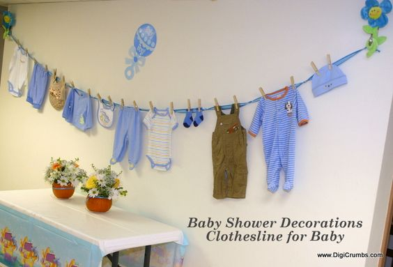 Have a clothesline of baby clothing in various teams for Baby shower clothesline decoration