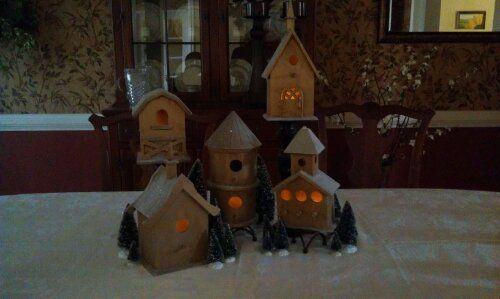 Took bird houses, covered the tops with fake snow and cut a hole in the bottom for a candle. Then put then on candle sticks at various heights, added some fake tree ad now it's a dining room center piece :)