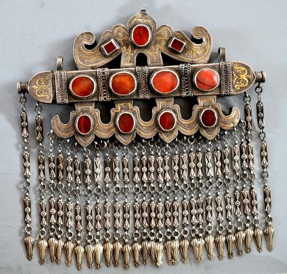 A keikel, Karakalpakstan. It resembles a Turkoman tumar, but is different. It has, horizontally, a tube (also found in the tumar) which is constructed as a kind of long box, with lid, to contain verses from the Koran. Those would protect the wearer. Karakalpak jewellery is scarce, and often of high quality, so is much collected. This is a fine example, from Linda Pastorino, who is keeping it in her private collection. The workmanship and the design are outstanding, and the condition is fine.