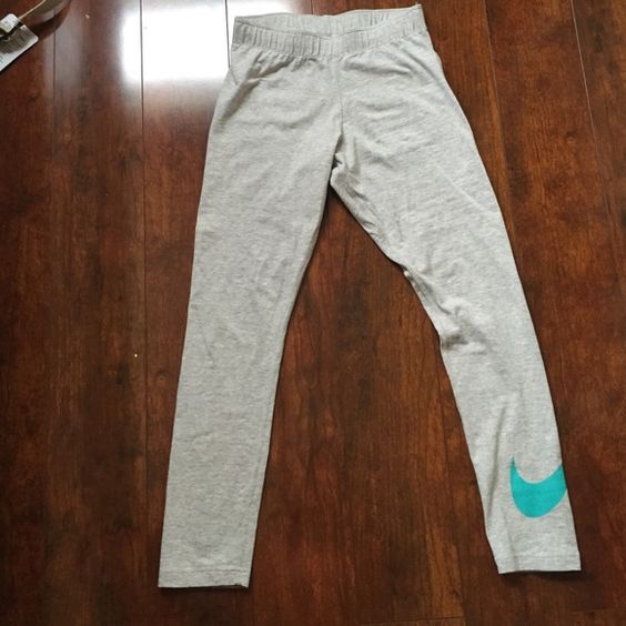 NWOT Nike Leggings Never worn, perfect condition. Teal Nike swoosh at the bottom. Size XS Nike Pants Leggings