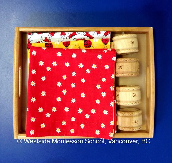 Montessori Practical Life activity - rolling a napkin. The environment and the materials must be appealing to the child. The children just love the fabric on the handmade napkins! The napkins rings are wood finished with beeswax, smooth to the touch.