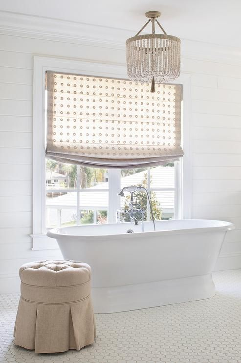 Beige Beaded Chandelier Hanging Over A Freestanding Tub And A