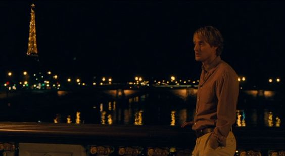 The Eiffel Tower lights up behind Gil Pender (Owen Wilson) on another magical evening