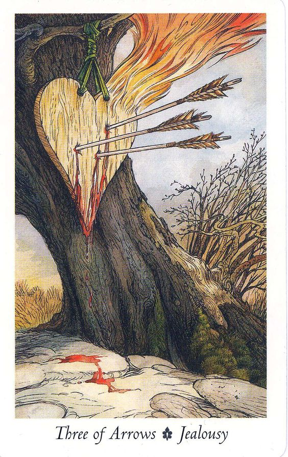 "The Three of Swords in general refers to feelings of sadness, loneliness, suffering and pain. In this version though the word ""Jealousy"" is associated with the card, adding a whole new layer. Here we see a wooden heart hanging from a rope that's been tied to the limb of a tree. Three arrows are piercing the heart — and drawing blood — while flames shoot out from the side. The heart looks old and weathered, the tree looks deprecate, the grass and brush surrounding it looks dead."