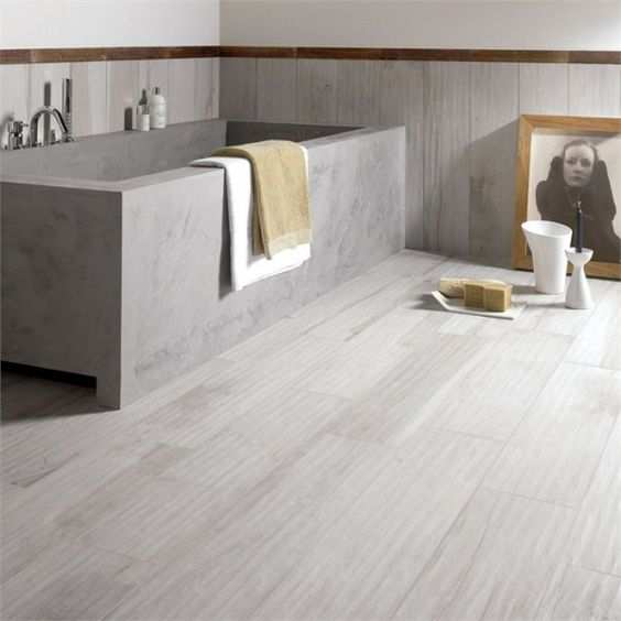 """12 Concrete Interiors: The wood-like effect and gray tone of these """"Soleras"""" ceramic floor tiles by ABK work well with the contemporary concrete soaking tub in this no frills bathroom."""