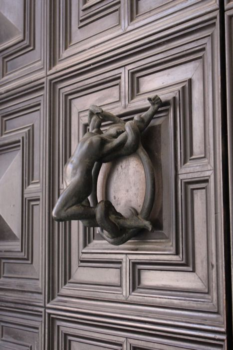 Srruggling woman door knocker photographed in Italy