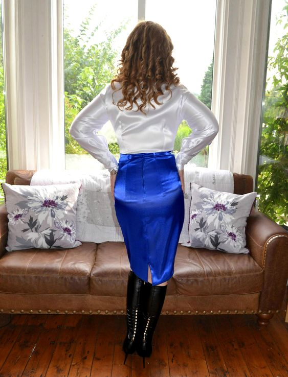 Back view of white satin blouse with satin skirt and black leather boots.