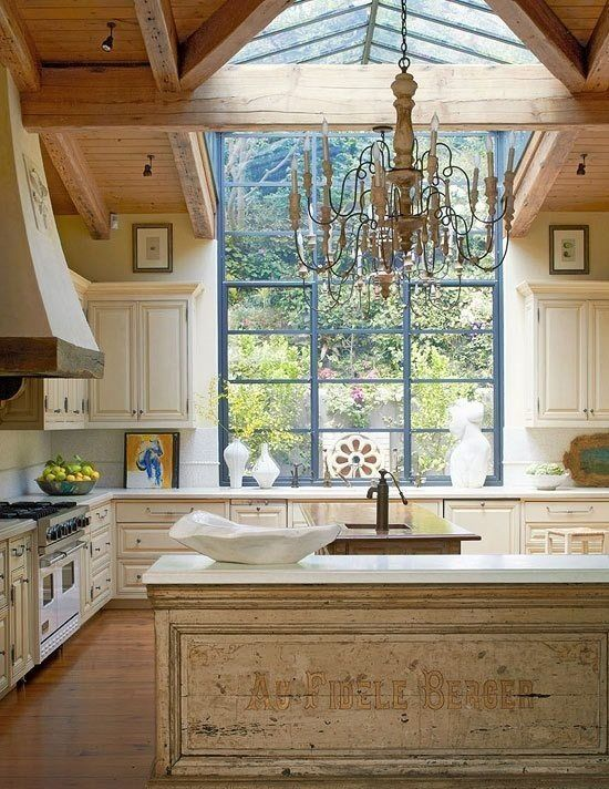A stunning example of French Country mixed with modern farmhouse style in this rustic kitchen. Modern steel windows left unadorned and a wood ceiling mix with creamy painted cabinets and an antique work table. #farmhousestyle #Frenchkitchen #Frenchcountry #kitchendesign